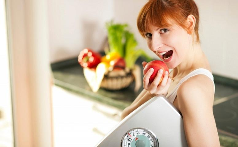 woman-holding-apple-and-weighing-scale.jpg