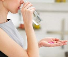 photo-of-woman-holding-glass-of-water-and-pills.jpg