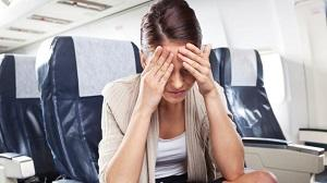 woman-in-plane-holding-her-head.jpg