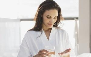 woman-holding-a-glass-of-water-and-pills.jpg