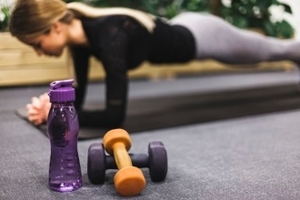 Close-up of water bottle and dumbbells in front of woman doing push ups