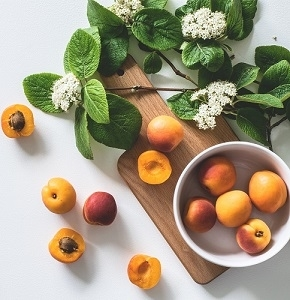 bunch of apricot fruits near flowers