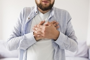 Man in grey shirt having heart attack